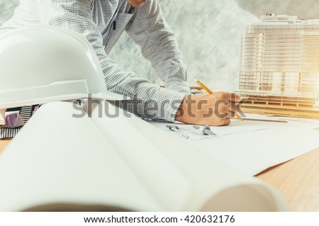 Architect working on blueprint. Architects workplace - architectural project, blueprints, ruler, helmet and divider. Construction concept. Engineering tools - stock photo