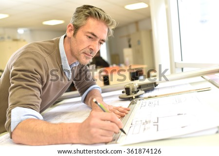 Architect working on drawing table in office - stock photo