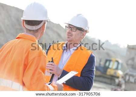 Architects discussing at construction site on sunny day - stock photo