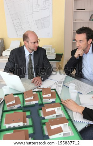 Architects gathered around a desk exchanging ideas - stock photo