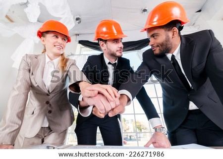 Architects laid hands on hands. Three businessmen architect met in the office to discuss business projects. Successful young people in the construction helmets are on the table - stock photo