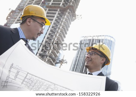 Architects looking at blueprint on construction site - stock photo