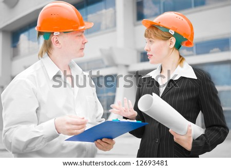 architects man and woman  protective helmet standing in front of a building - stock photo