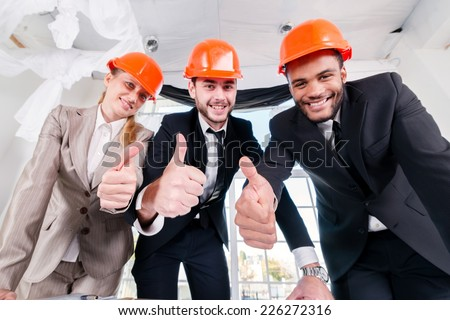 Architects show thumbs up. Three businessmen architect met in the office to discuss business projects. Successful young people in the construction helmets are on the table - stock photo
