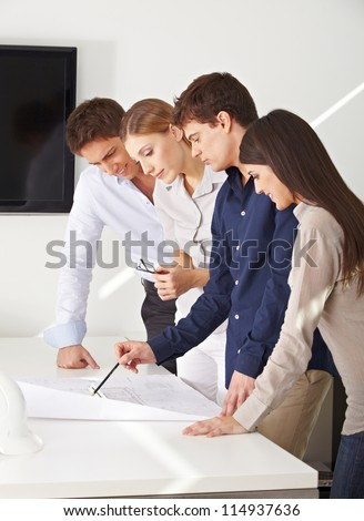 Architects team working on construction drawing in their office - stock photo