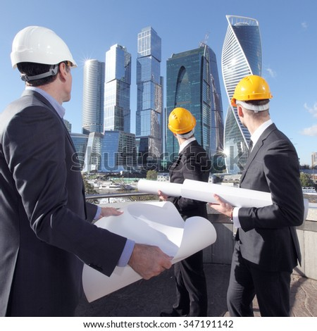 Architects with blueprint at skyscrapers background - stock photo