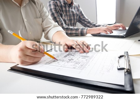 Architects working on blueprint real estate stock photo safe to use architects working on blueprint real estate project architect workplace architectural project blueprints malvernweather Choice Image