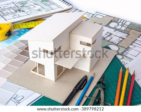 Architects workspace with small house model & drawing sketch/ home renovation concept - stock photo