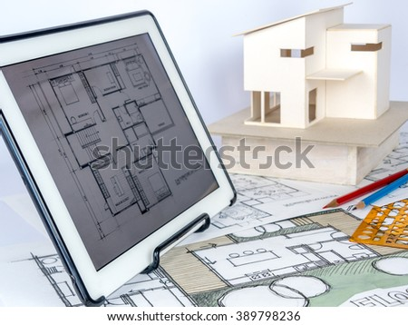 Architects workspace  with tablet, small house model, drawing & blueprints/ home renovation concept - stock photo