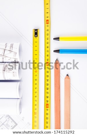 architectural accessories. yellow hardhat, measure, pencils, plans