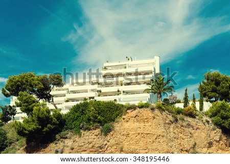 Architectural apartment building in beautiful holiday resort area for tourists.  Vacation flats and hillside condominium construction on Spanish Majorca island, image is filtered for special effect - stock photo