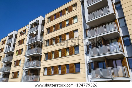 Architectural background of a modern stylish  apartment building, white facade decorated with wood against blue sky - stock photo