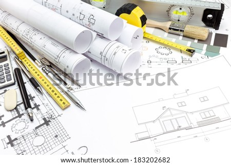 Architectural background with technical drawings and work tools - stock photo