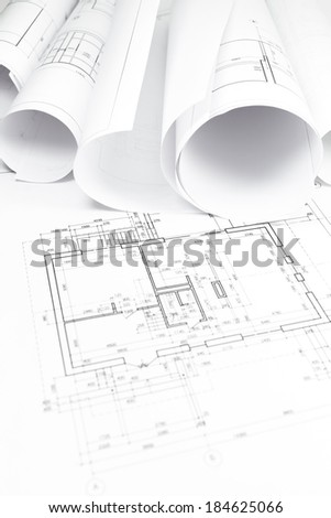Architectural blueprint with bunch of rolled up building plans