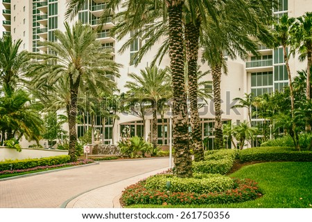 Architectural buildings Miami Style South Beach Florida image retro filtered   Palm-lined driveway in front luxury residential apartment skyscraper for real estate business website blog magazine book - stock photo