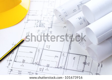 Architectural construction plans with pencil and hardhat on it - stock photo