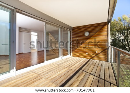 architectural contemporary - sunlit balcony with wooden floor and wall of an apartment building in green area. - stock photo