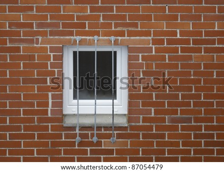 architectural detail of a barred window in a red brick wall