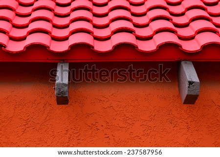 Architectural detail of colorful building exhibiting the Spanish or Mexican influence with roof tiles, stucco walls and wooden beams.