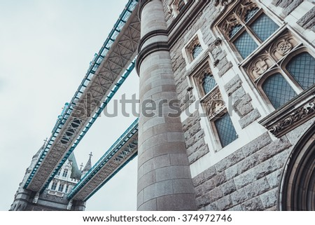 Architectural detail of the Tower Bridge, London looking up the stone facade of one of the towers to the pedestrian walkway - stock photo