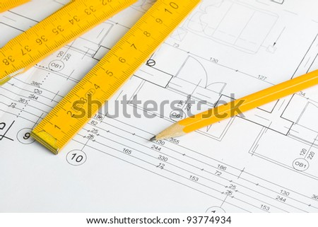 Architectural drawing, pencil and yellow wooden measurement tape - stock photo