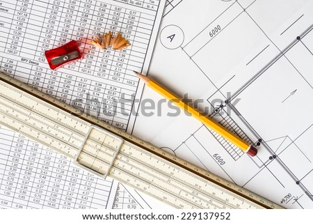Architectural drawings, slide rule and a sharpener with a pencil - stock photo