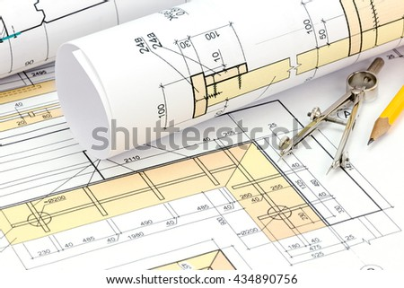 architectural plans and technical drawings with rolls of blueprints  - stock photo