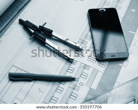 Architectural project, rulers, cell phone and pen. - stock photo