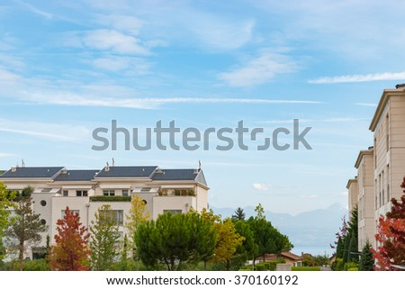 Architectural residential building with modern rental apartments  Modern condo building with windows and venetian blinds built. Green plants trees and grass in front - stock photo