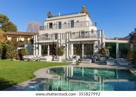 Architecture; beautiful house with pool, blue sky and lush garden  - stock photo