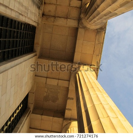 Architecture concept. Classical frontis from above: low angle view of a ceiling and a pair of columns. Blue sky at background