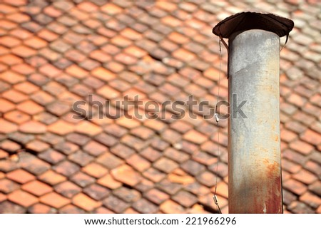 Architecture detail with rusty tin chimney and tile roof on the background - stock photo