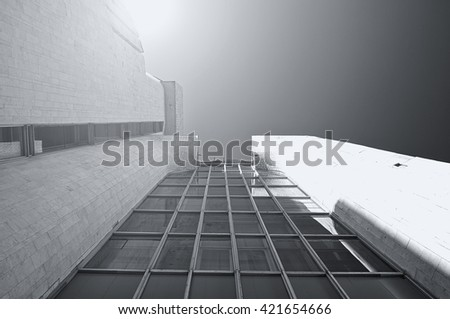 Architecture futuristic background - perspective bottom view of high  tech designed building of concrete and glass under sunlight. Black and white tones applied. Architecture cityscape.  - stock photo