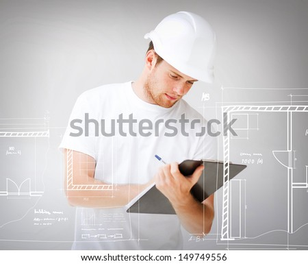 architecture, interior design and renovation concept - male architect in helmet looking at blueprint - stock photo