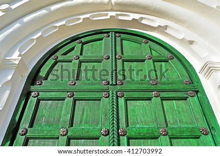 Architecture texture background. Vintage wooden bright green door with metallic rivets and upper arch of white stone - colored architecture background - stock photo