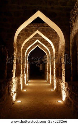 Archway inside Bahrain fort at night - stock photo