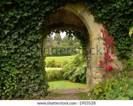 Archway of stone with view of English garden - stock photo