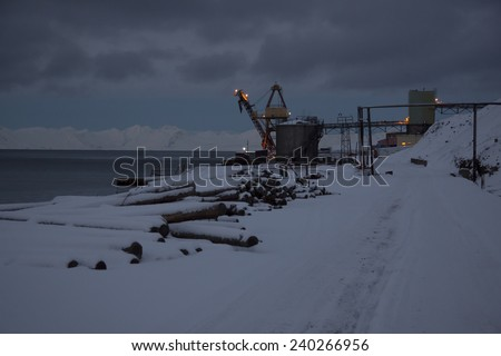 Arctic port in the Russian settlement of Barentsburg on Spitsbergen in the initial period of the polar night, a small ship in the port - stock photo