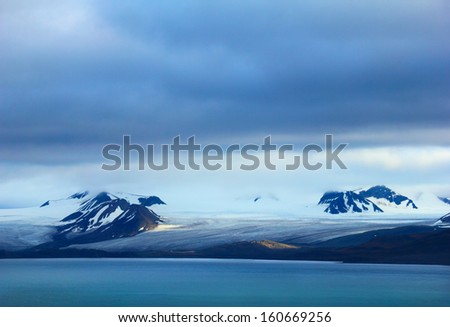 Arctic scene - melting glacier, black mountains covered with snow and blue gulf against background of dramatic sky near Barentsburg, Spitsbergen archipelago (Svalbard island), Norway, Greenland sea  - stock photo