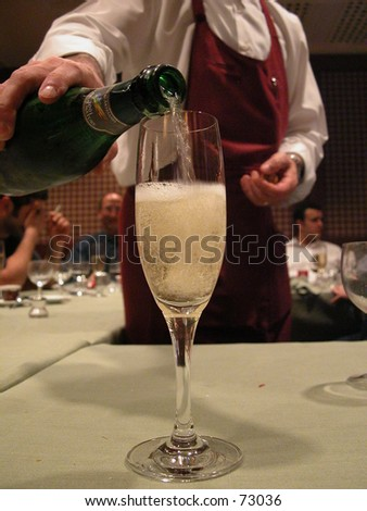 Are you being served? Waiter serving a glass of chilled champaign - stock photo