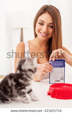 Are you hungry? Beautiful young woman opening a pack with cat food and smiling while little kitten waiting while sitting on foreground