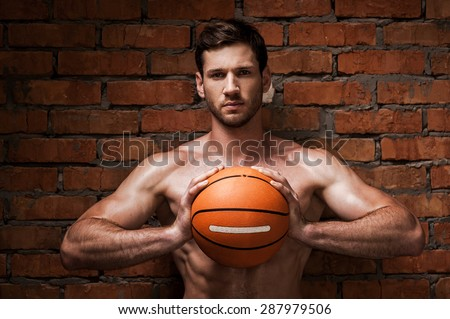Are you ready to play? Confident young muscular man holding basketball ball while standing against brick wall  - stock photo