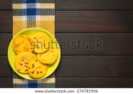 Arepa - Made of white or yellow corn meal, traditionally eaten for breakfast or as snack in Colombia and Venezuela. Photographed on dark wood with natural light, overhead shot - stock photo