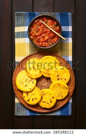Arepas (corn meal patties) on wooden plate with Colombian hogao or criollo sauce (tomato and onion cooked) in bowl. Photographed overhead on dark wood with natural light. - stock photo