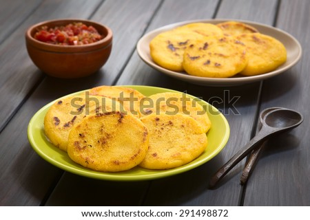 Arepas with Colombian hogao sauce (tomato and onion cooked) in the back. Arepas are made of corn meal and are traditionally eaten in Colombia and Venezuela (Selective Focus, Focus on the first arepas) - stock photo