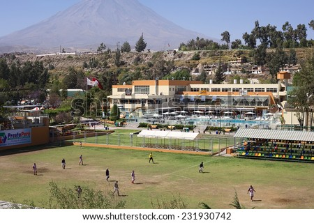 AREQUIPA, PERU - AUGUST 23, 2014: Unidentified men playing football on pitch at Club Internacional Arequipa (International Country Club) on August 23, 2014 in Arequipa, Peru (Volcano Misti in back)