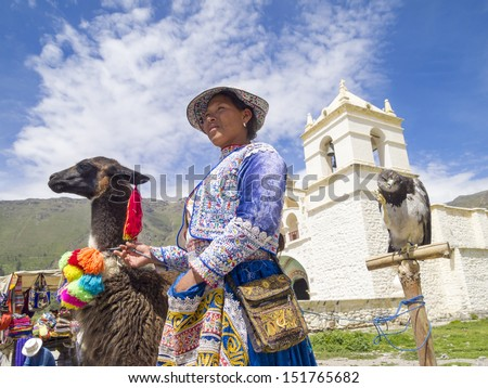 AREQUIPA, PERU - MAR 12: Unidentified Quechua indian woman with Alpaca and Hawk in front of the Church on Mar 12, 2011 in Colca canyon, Arequipa, Peru. Colca canyon is home to the Andean Condor. - stock photo
