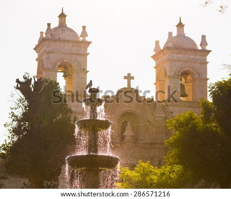 Arequipa, Peru:  The water pool of caima park and antique church as background, focus on the pool. - stock photo