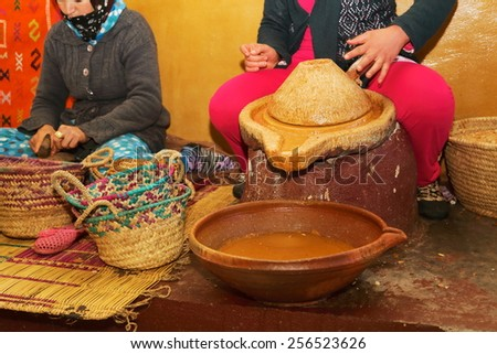 argan oil processing by hand by women used in cosmetics and food morocco - stock photo