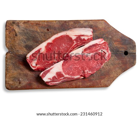 """Argentinean """"bife de chorizo"""" raw meat on wooden table. Clipping path excludes shadow. - stock photo"""